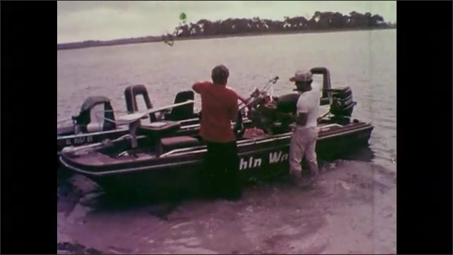 1970s: UNITED STATES: truck pulls trailer from water. Men load bike into boat. Man holds cup in hand. Boat by shore.