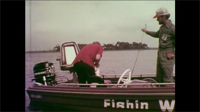 1970s: UNITED STATES: man catches large bass. Man sits and fishes from boat. Man removes bate from fish mouth.