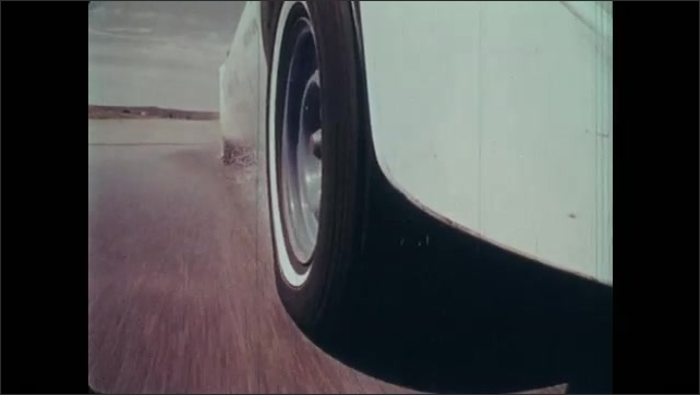 1970s: Display of tires. Car and tires rolling along dry and wet pavement. Sportscar weaves between traffic cones.