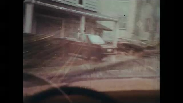 1970s: Cars and truck drive down rainy road. Car skids out of control on road. Bus lets out kids on rainy street. Cars come to stop on wet road. Kids cross road.