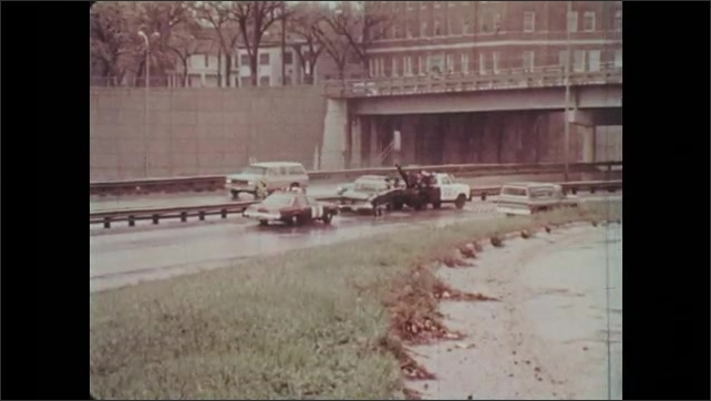 1970s: Car pulls on to busy road in the rain. Tow truck pulls wrecked car while police car follows.