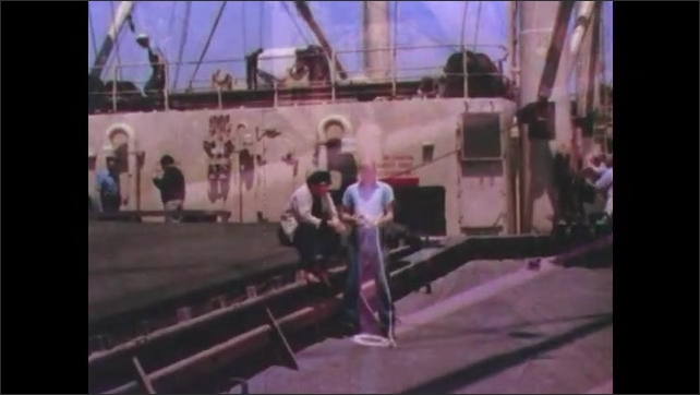 1950s: men in sailor hats work and water hose the deck of cargo ships. man in blue shirt practices knots on rope as boat helper with black hat sits on steps and watches.