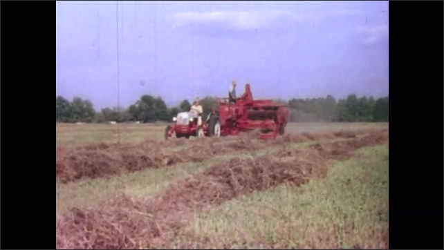 1950s: UNITED STATES: Farmer drives red combine harvester across field. Man ploughs field.