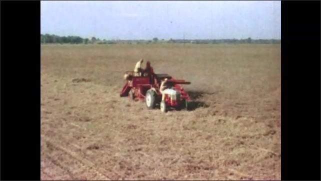 1950s: Farming equipment drives through field.