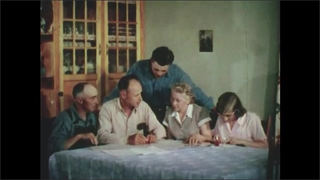 1950s: People around table, look at papers. Men use surveying equipment in field.