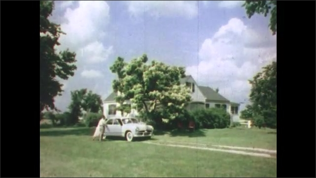1950s: Long shot of tractor in field. Men herding cattle into building. Long shot, man and woman get into car. Car drives down road. Exterior of school building.