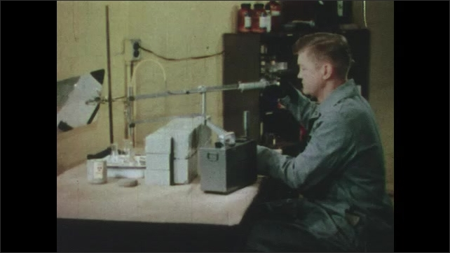 1950s: Hands cracks egg into dish. Man working with equipment in lab.