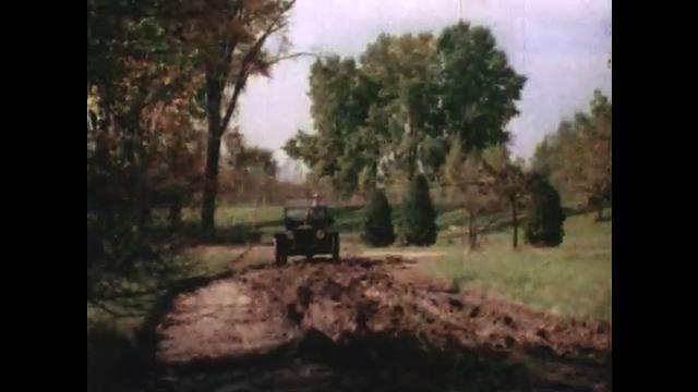 1950s: UNITED STATES: man drives car along muddy track