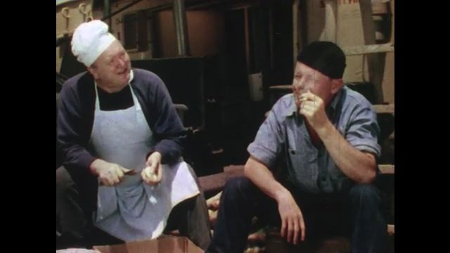 1950s: UNITED STATES: man peels potatoes on deck of ship. Man smokes on ship. Men relax and work on deck of ship.
