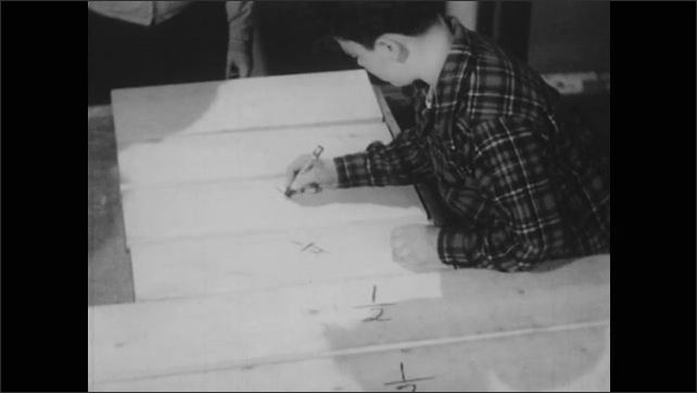 1940s: Man and boy stand at work bench. Boy with pencil points to lengths of board. Hand writes fraction on board with pencil. Boy writes fractions on boards.