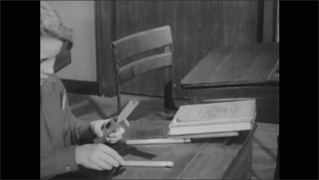 1940s: Boy walks into classroom and sits at desk. Boy divides box of pencils at school desk. Hands place pencils into three equal piles on desk.
