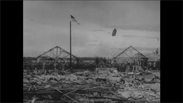 1940s: UNITED STATES: island destroyed by enemy. American flag on pole.