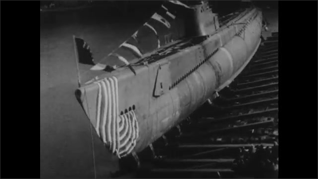 1940s: UNITED STATES: torpedo fired into sea. Submarine in water. View of ship from submarine periscope.