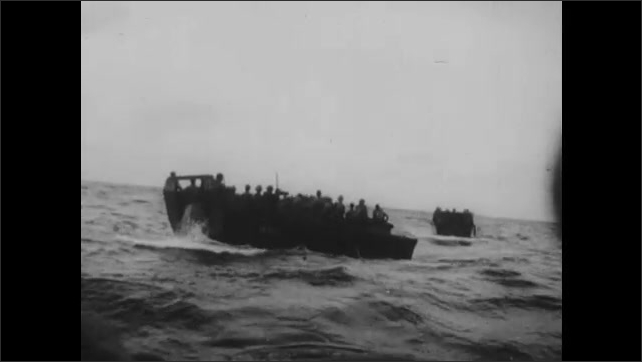 1940s: UNITED STATES: Navy personnel on water. Rockets fire from boat. Explosives strike island.