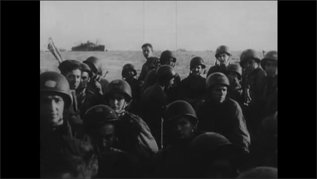 1940s: UNITED STATES: Navy men on landing boats. Fleet prepare to land on shore. Explosions along coastline.