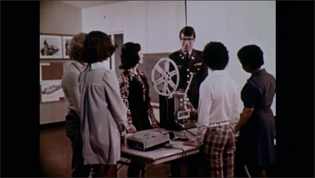 1970s: Army officer talks to teacher and students around film projector table. Students smile. Army officer talks to teacher and students around film projector table.