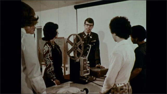 1970s: Army officer gesticulates and talks to teacher and students around film projector table.