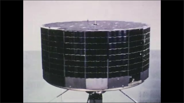 1960s: UNITED STATES: equipment rotates on spot. Panels on satellite. Internal workings of dish.