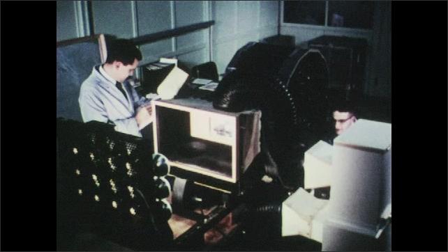 1960s: UNITED STATES: men work in science laboratory, Engineers work on meteorology equipment.