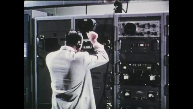 1960s: UNITED STATES: satellite dish receives signals. Man works at control panel. Man listens to headset. Photos of weather in developing fluid