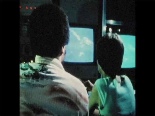 1970s: Person's hands on video controls. Monitor with map on it. Two people working controls, looking at map on monitor.