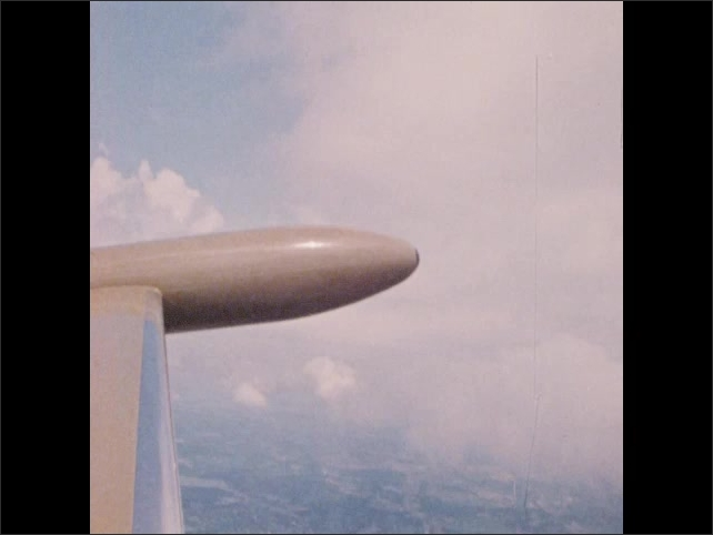 1970s: Two men look out window of airplane. Looking at wing of plane in sky. Illustration of airstream.