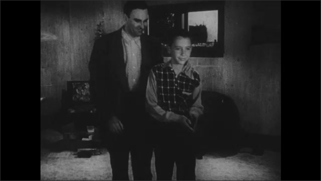 1950s: Man and boy talk in living room while boy rolls measuring tape up that was spread across the floor. They walk out of room. Boy runs and climbs over fence while waving.