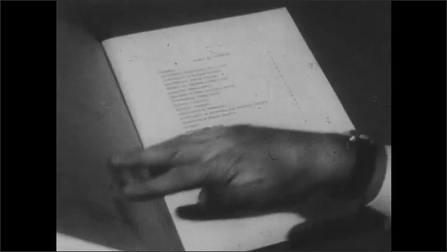 1950s: Television radio tower climbs into sky. Hand flips through booklet on desk.