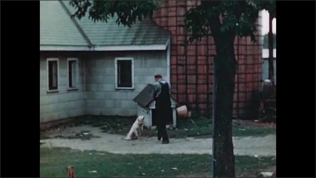 1940s: UNITED STATES: farmer leaves house. Farmer walks across yard. Farmer strokes dog by kennel. Farmer milks cow.