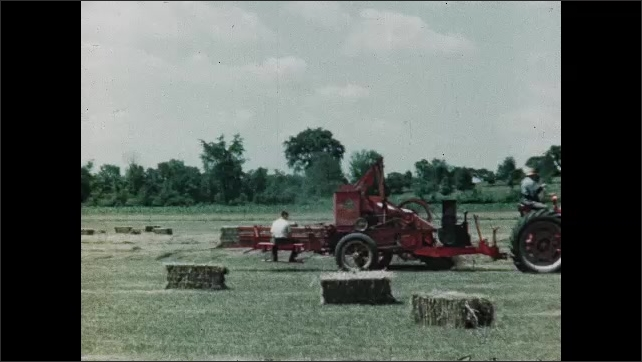 1940s: UNITED STATES: hay bailer in field. Farmer drives tractor in field. Boy its on back of trailer. Boy shouts at man in tractor. Hay bail falls off vehicle.