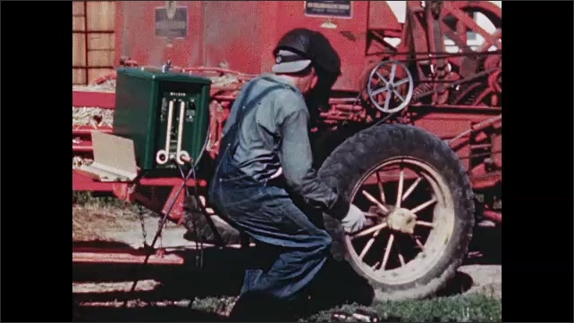 1940s: UNITED STATES: farmers weld broken part on tractor. Man wears face screen whilst welding. Close up of welded metal on tractor.