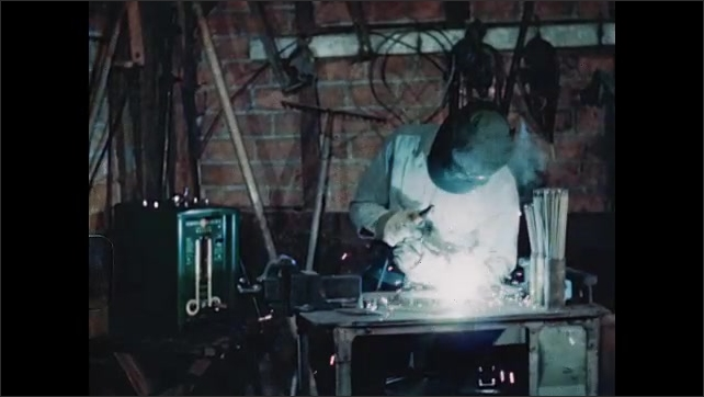 1940s: UNITED STATES: man arc welding on bench. Welding operator wears safety mask.