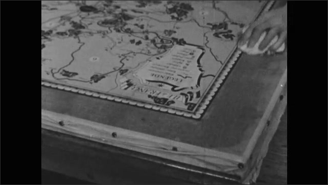 1950s: Hands press edges of map wih rolling pin. Hands pick up paper, wipe map. Man wipes map.