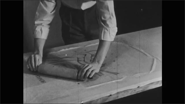 1950s: Hands roll paper with rolling pin, pull up corners. Hands flatten paper with roller. Hand rolls over strips of paper.