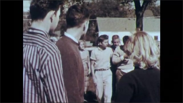 1950s: UNITED STATES: students argue outside school. Boys fight. Crowd gathers around boy. Boy wipes bloody nose