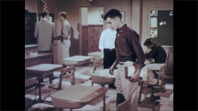 1950s: UNITED STATES: boy arrives in class. Boy points at desk.