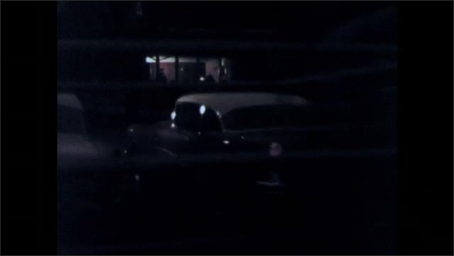 1950s: UNITED STATES: car drives along road at night. Car parks by building. Young people in car.