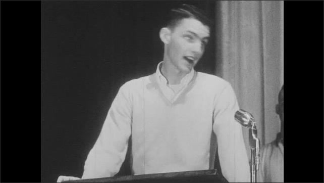 1950s: Teen girl introduces teen boy captain at podium. Basketball team captain speaks sincerely.