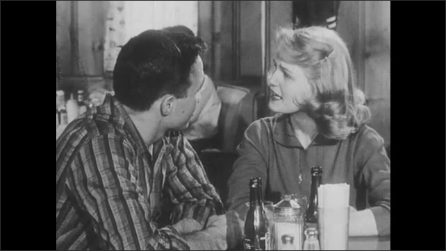 1950s: Girl cousin talks intensely with teenage boy cousin, challenging him.