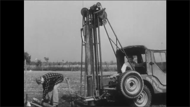 1960s: UNITED STATES: farmer digs post hole in ground. Man with machine. Man digs hole.