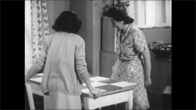1950s: Woman sews as girl watches, holding apple. Woman stands and moves chair to table. Woman and girl sit down. Woman holds magnifying glass over fabric sample. Girl gestures at fabric sample.