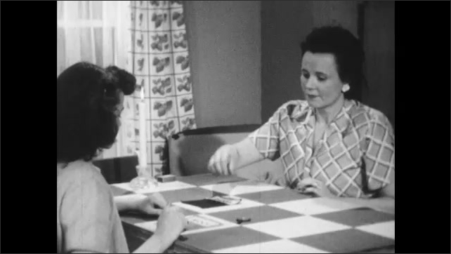 1950s: View of magnified material. Girl picks up thread and looks at it. Fingers rub soot. Woman picks up thread, smells it, and puts it down in front of girl. Woman picks up cloth.