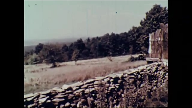 1960s: Man walks across stage. Man points and speaks. Panorama of farmland and stone wall. River flows.