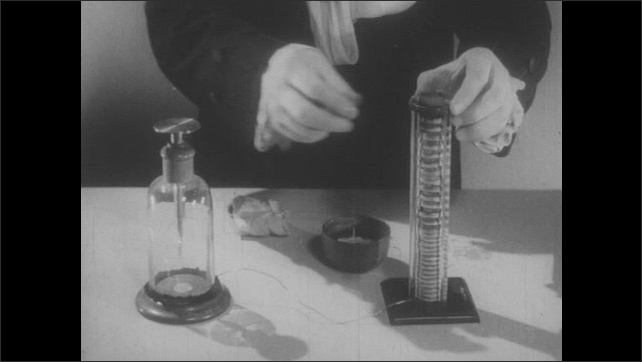 1950s: Table with scientific apparatus. Hands stack small disks. Hand attaches wire to top of stack.