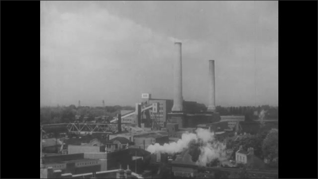 1950s: Train moves past large industrial complex. Cars and trucks drive by industrial building.