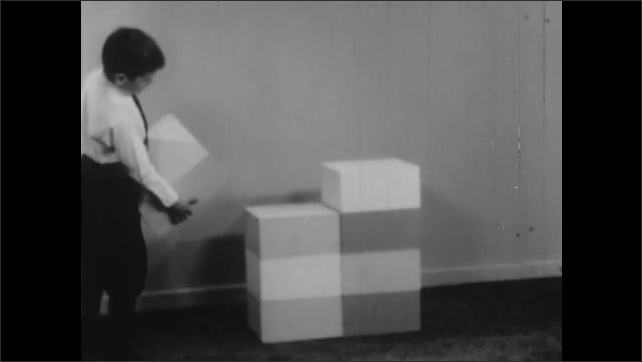 1940s: UNITED STATES: children build tower from blocks. Boy adds block to tower. Girl start new pile of blocks