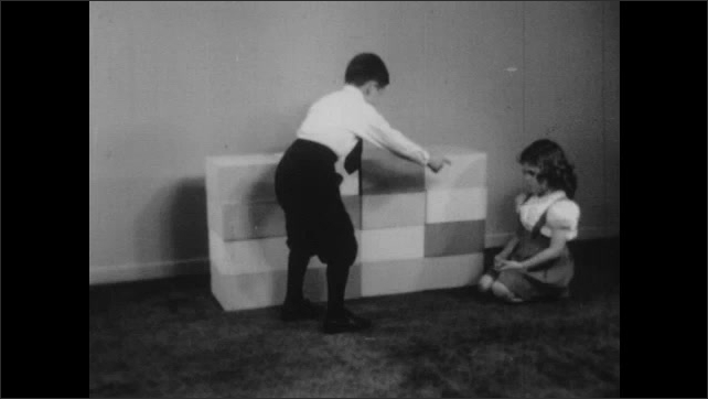 1940s: UNITED STATES: girl counts tower of blocks. Boy counts row of blocks.