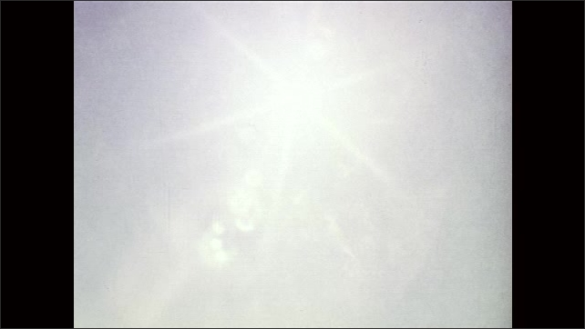 1960s: UNITED STATES: clouds move across sky. Trees blow in wind. Sunlight behind leaves in tree. Grass in field. Horse title. Horse runs across field