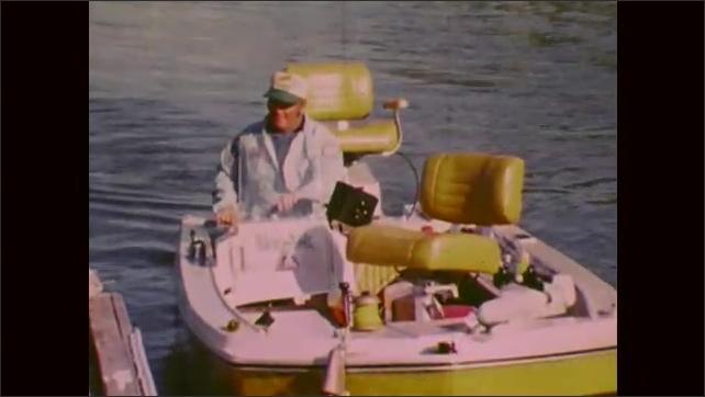 1970s: Lake.  Man docks fishing boat.