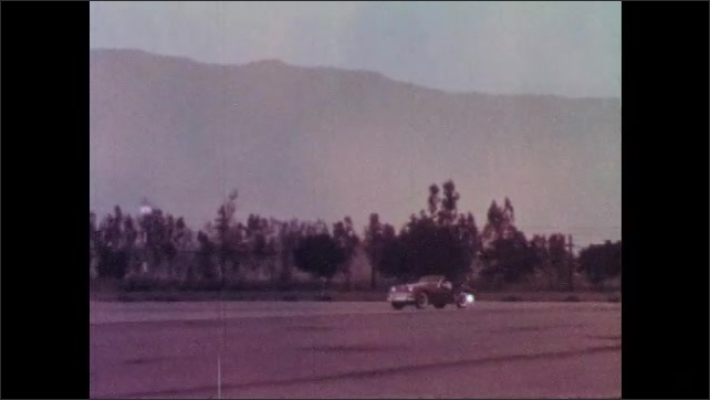 1960s: Light spins on rear tire of car. Car drives along tree-lined road.